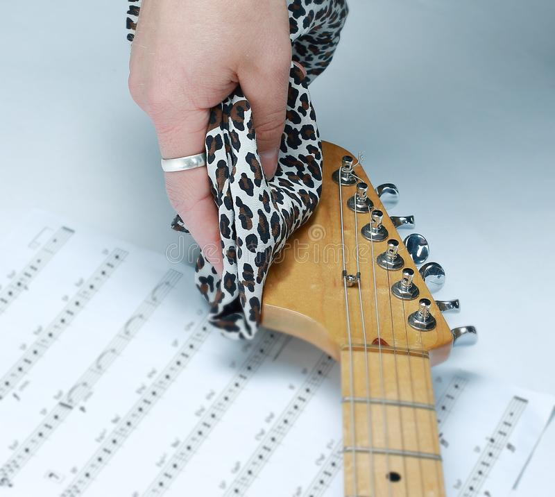 Closeup.rock guitarist,wiping the neck of the guitar royalty free stock photography