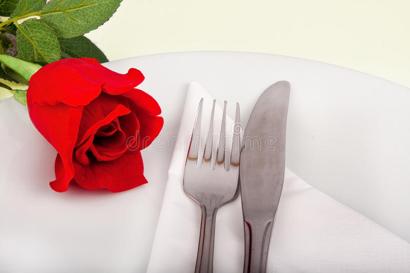 Closeup of rose, plate and silver cutlery royalty free stock images