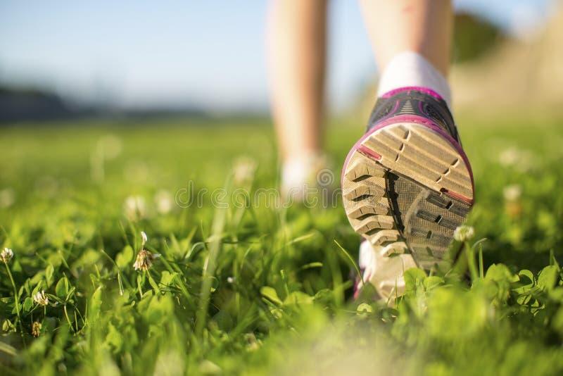 Closeup runner feet running outdoors on the green grass. Fitness. royalty free stock photos