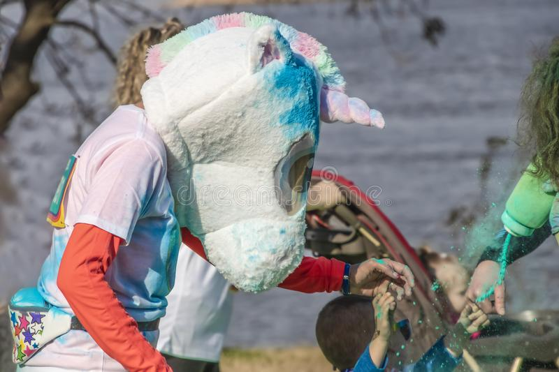 Closeup of runner with fuzzy unicorn head being squirted with colored powder in a holi-color run with blurred children and river royalty free stock image