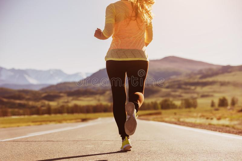 Closeup running woman straight road royalty free stock images