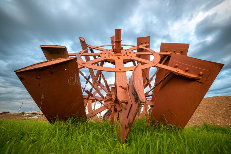 Rural landscape with vintage paddle steamer blades on grass and blue thunderstorm sky stock images
