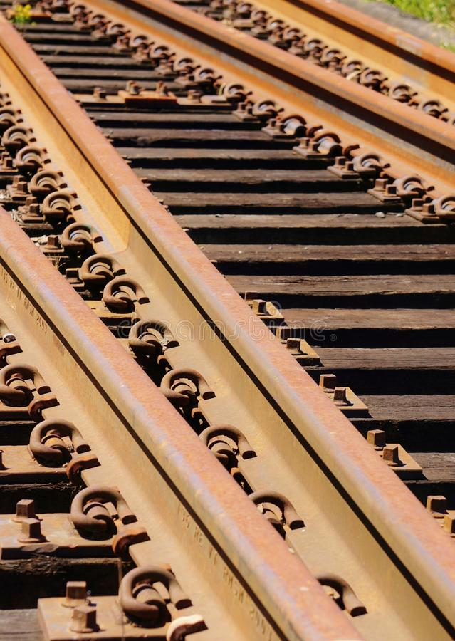 Closeup of Rusted Unused Railroad Tracks. Detail shot of unused salvage portion of railroad track and ties merging. The angles of the tracks and repetitive stock photos