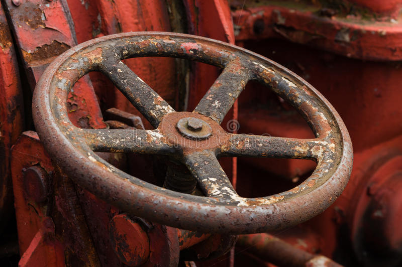 Closeup of rusty old metal valve on weathered red machine.  stock image