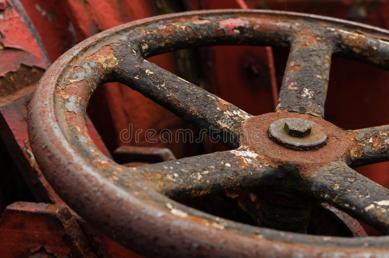 Closeup of rusty old metal valve on weathered red machine.  royalty free stock photos