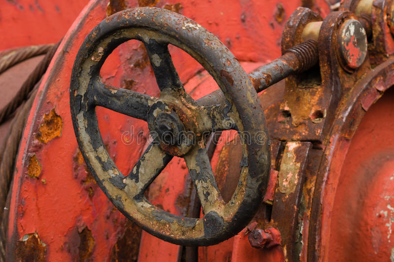 Closeup of rusty old metal valve on weathered red machine.  stock images