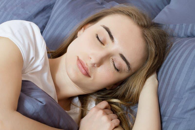 Closeup - sömn sova kvinnabarn f?r underlag Stående av härligt kvinnligt vila på bekväm säng med kuddar, i att bädda ned in arkivfoton