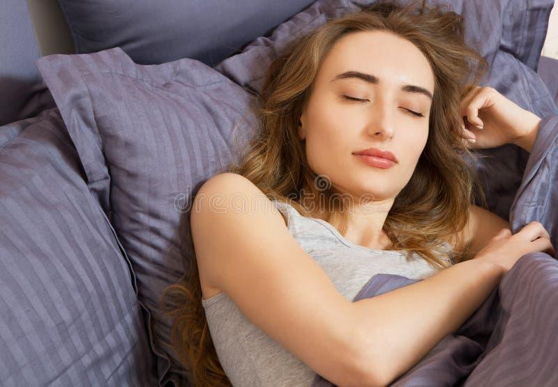 Closeup - sömn sova kvinnabarn f?r underlag Stående av härligt kvinnligt vila på bekväm säng med kuddar, i att bädda ned in royaltyfri bild