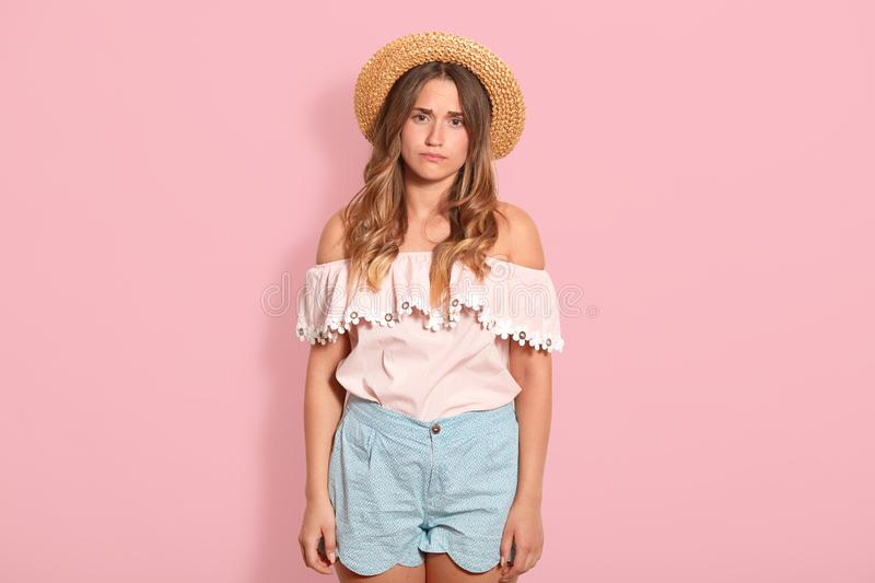 Closeup of sad pensive young woman with long wavy hair and straw hat, wearing summer clothes, looks unhappy, feels bad, looking royalty free stock photography