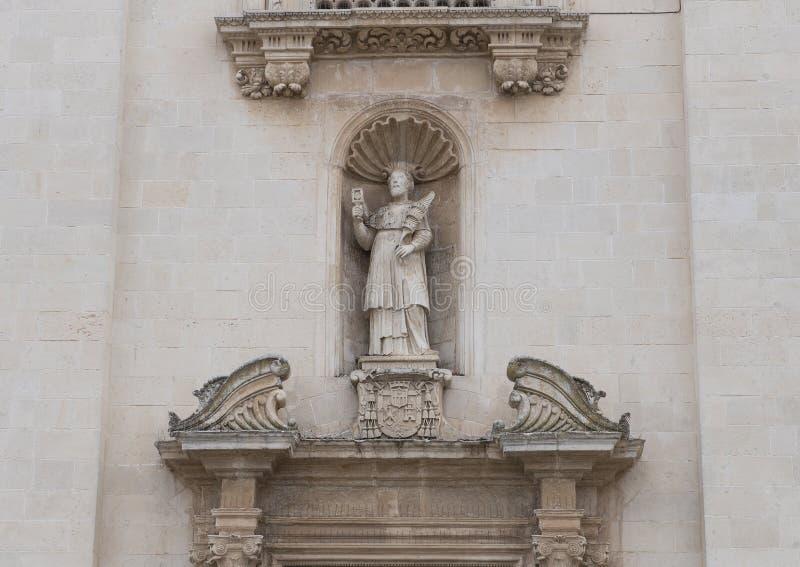 Closeup of Saint in a niche above right door, Front of the Chiesa Madre dei Santi Pietro e Paolo Galatina Italy stock photo