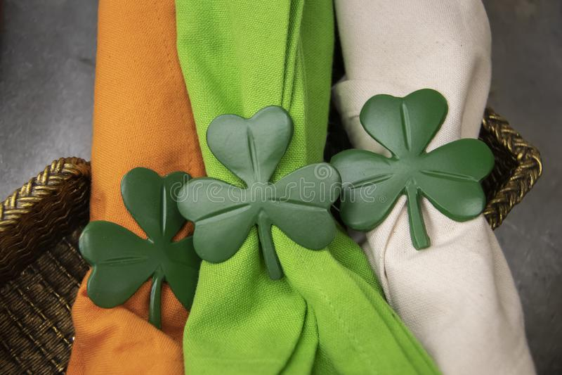 Closeup of Saint Patricks Day shamrock napkin holders on bright orange green and white cloth napkins in gold basket royalty free stock photos