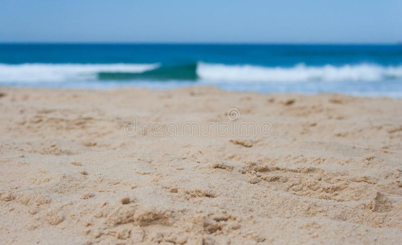 Closeup of sand at the beach on a sunny summers day in landscape format. With wave breaking stock photography