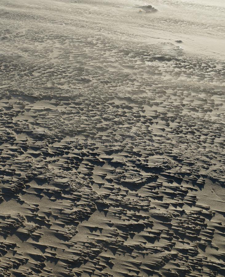 Regular structures of sand drifts on a wind-swept beach stock photo