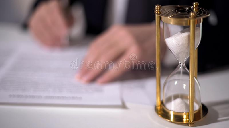 Closeup of sand clock measuring time, official signing important reform document. Stock footage stock images