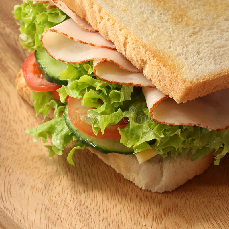 Closeup sandwich. A closeup of a delicious appetizing fresh and healthy light lunch sandwich with two slices of white bread, ham, cucumber, tomatoes and lettuce royalty free stock images