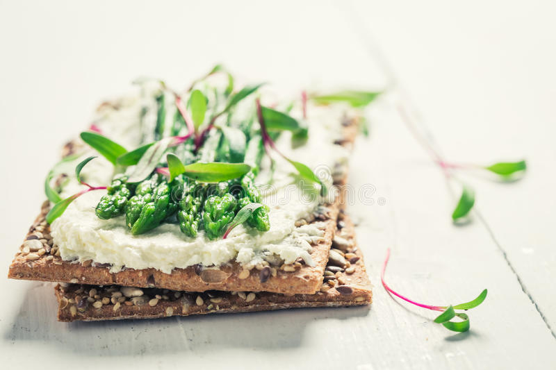 Closeup of sandwich with asparagus and fromage cheese. On white wooden table royalty free stock images