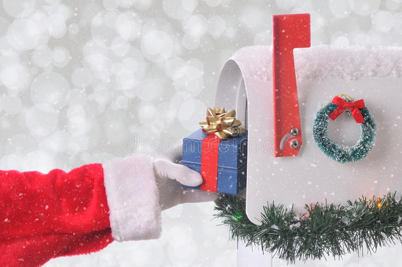 Closeup of Santa Claus placing a small present into an open mail box. Horizontal format wih a silver bokeh background and snow effect stock image