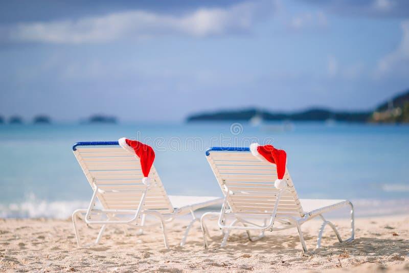 Closeup santa hat on chair on tropical white beach. Red santa hats on chair longues at tropical white beach royalty free stock photo