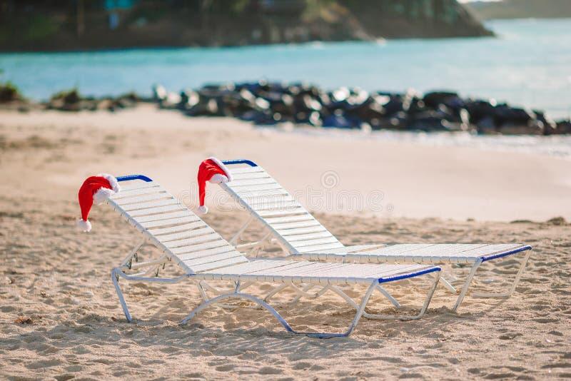 Closeup santa hat on chair on tropical white beach. Santa hats on chair longues at tropical white beach stock photo
