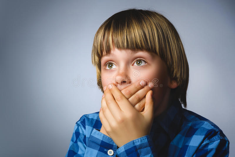 Closeup Scared and shocked little boys. Studio shot portrait over gray background. Human emotion face expression. Life royalty free stock image
