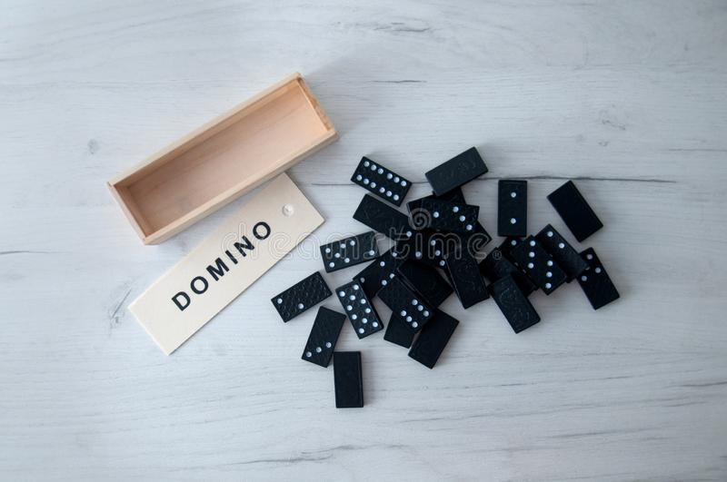 Closeup scattered dominoes on a gray, wooden table. stock photo