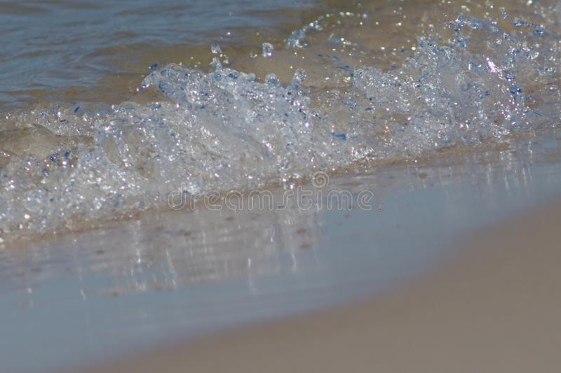 The closeup of the sea wave reaching the shore showing individual drops and splashes stock photography