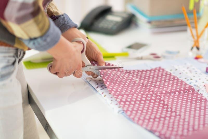 Closeup on seamstress cutting fabric. On table stock photos