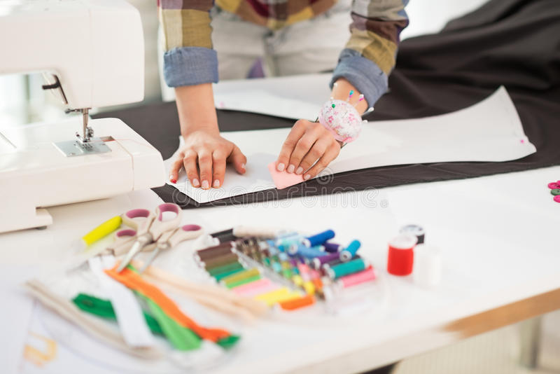 Closeup on seamstress making pattern on fabric. On table royalty free stock photo