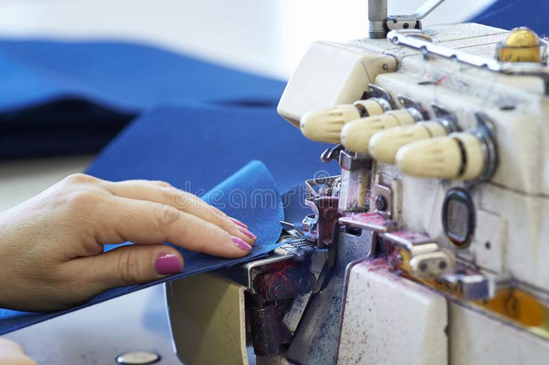 Closeup of a seamstress`s work on an overlock in a sewing worksh. Op. Tailor-made hands sew fabrics on the sewing machine royalty free stock photography