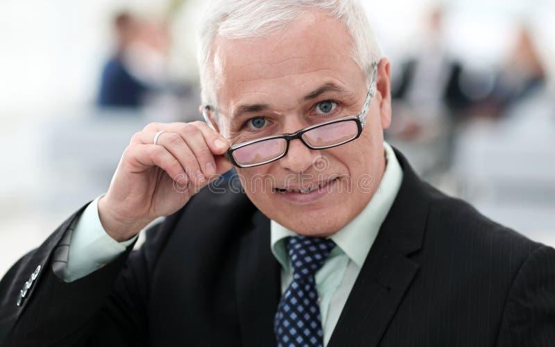 Closeup of a senior businessman adjusting his glasses royalty free stock photo