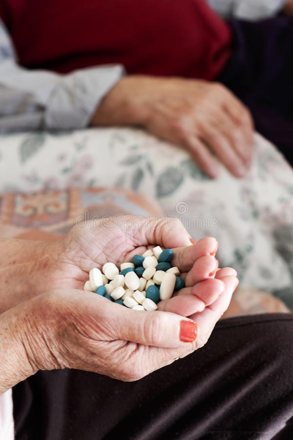 Senior woman with a pile of pills in his hand royalty free stock photos