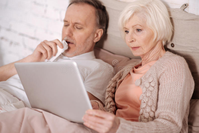 Closeup of senior couple lying on bed. Trying to entertain. Elderly women lying on bed near her coughing husband and holding laptop royalty free stock photography