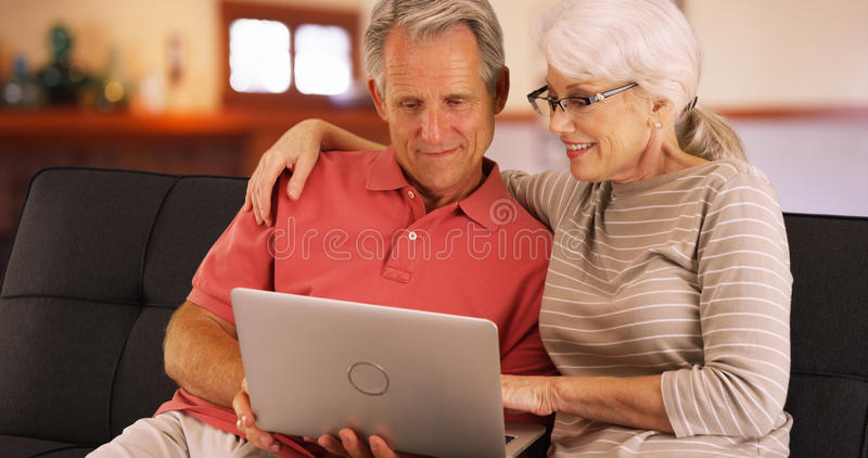 Closeup of senior couple using laptop at home royalty free stock images