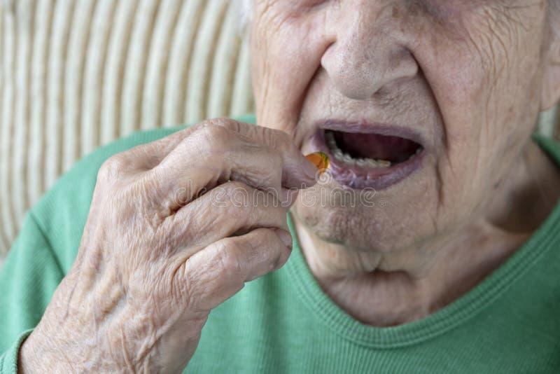 Closeup of a senior person taking a vitamin capsule stock image