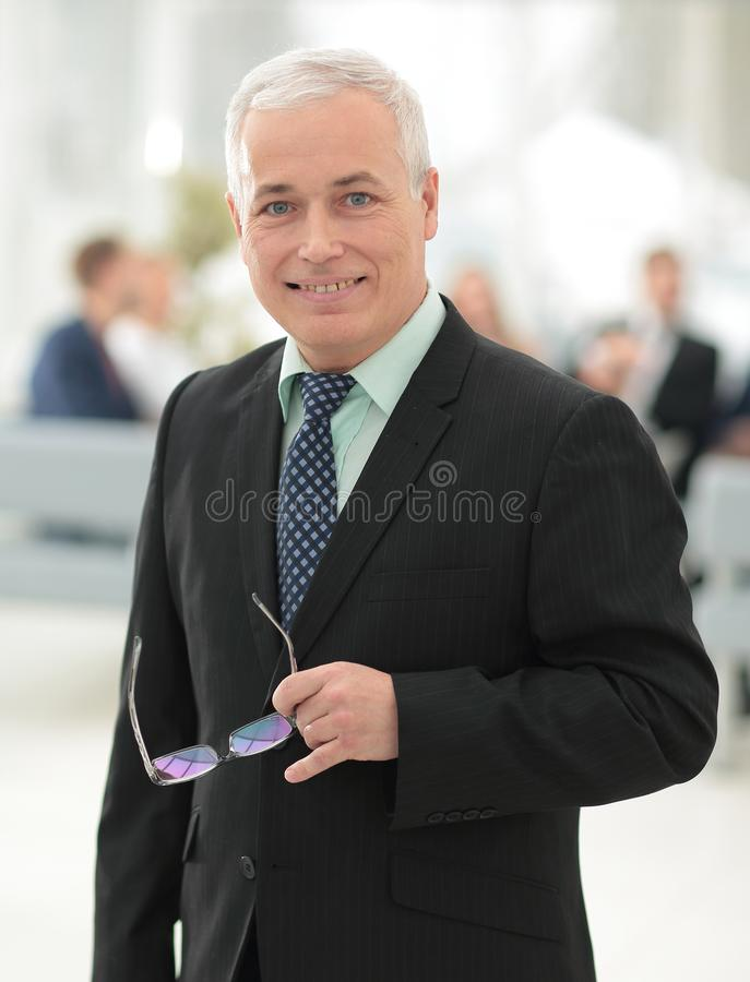 Closeup of a serious senior businessman with glasses in hand. royalty free stock photography