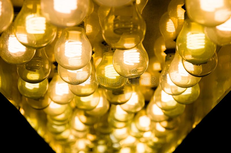 Closeup of several yellow gold lightbulbs shining in the dark royalty free stock image