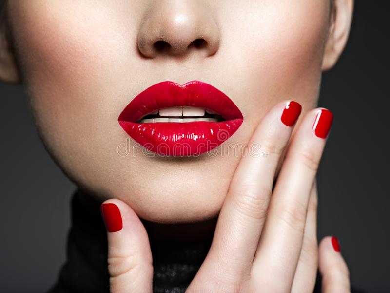 Closeup female lips with red lipstick. Glamour fashion bright gloss make-up and manicure royalty free stock image