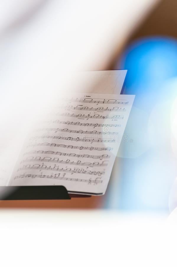 Closeup of sheet music in white bright background with colorful flares and selective focus stock image