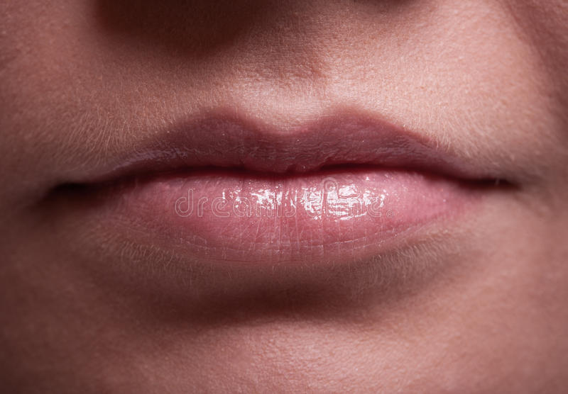 Closeup shiny female lips. Part of face. Makeup and beauty. stock photo