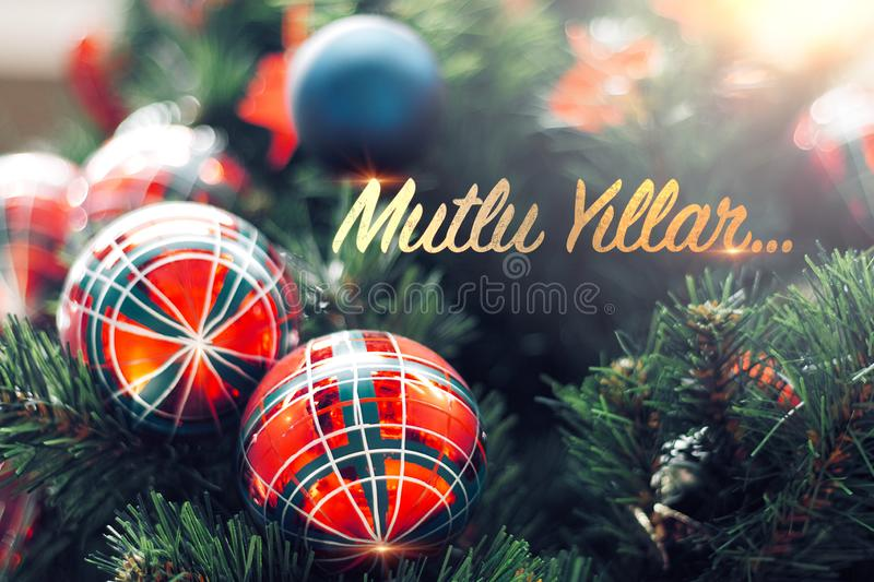 Closeup of shiny red bauble hanging from a decorated Christmas tree. Mutlu Yillar means Happy new year stock photos