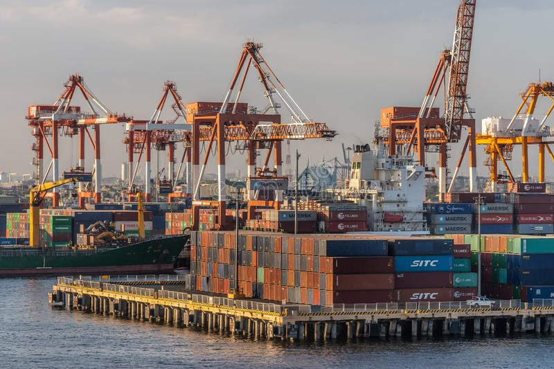 Closeup of Shipping containers, multiple cranes and ships in Manila, Philippines. Manila, Philippines - March 5, 2019: South Harbor evening twilight. Closeup of stock image