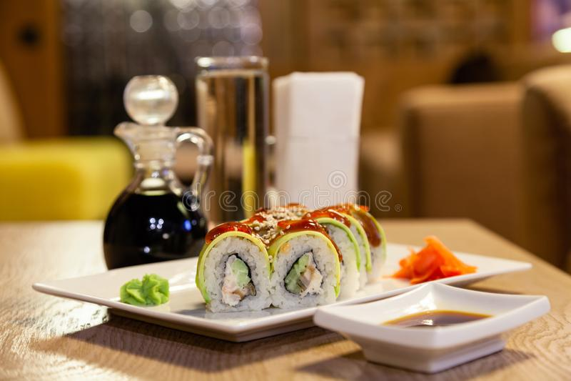 Closeup shogun sushi roll with avocado, strawberry, teriyaki sauce, sesame, wasabi, ginger, white Japanese plate, soy sauce, white stock photo