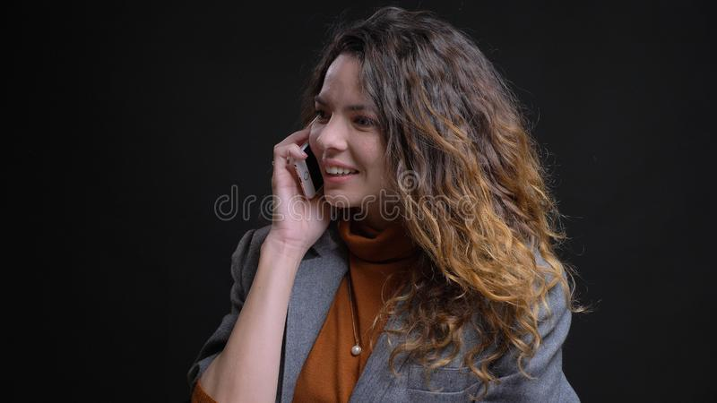 Closeup shoot of young attractive caucasian female having a phone call and cheerfully smiling in front of the camera royalty free stock image