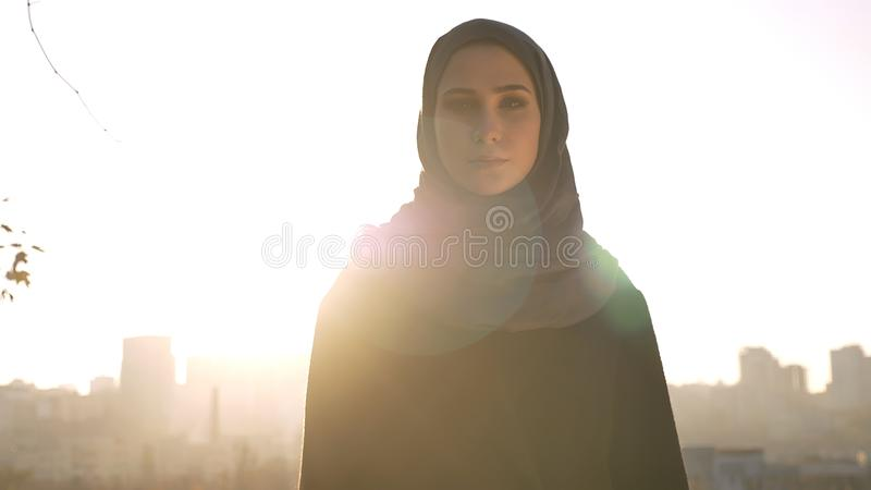 Closeup shoot of young attractive female silhouette in hijab looking straight at camera with urban city on the royalty free stock photo