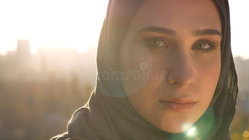 Closeup shoot of young attractive muslim female in hijab looking forward with urban setting and shining sun on the royalty free stock images