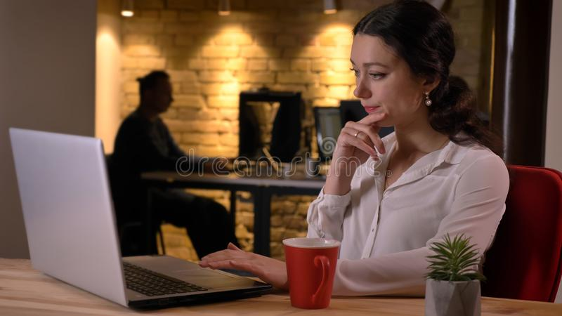 Closeup shoot of young busy caucasian businesswoman typing on the laptop being concentrated an focused indoors on the royalty free stock photos