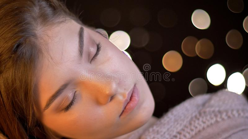 Closeup shoot of young feminine caucasian brunette female with her eyes closed being joyful and relaxed with bokeh royalty free stock images