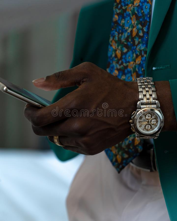 Closeup shot of an African male wearing green suit and a gray wristwatch holding a smartphone. A vertical closeup shot of an African male wearing green suit and stock photography