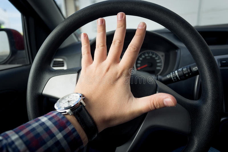 Closeup shot of angry driver honking in traffic royalty free stock image