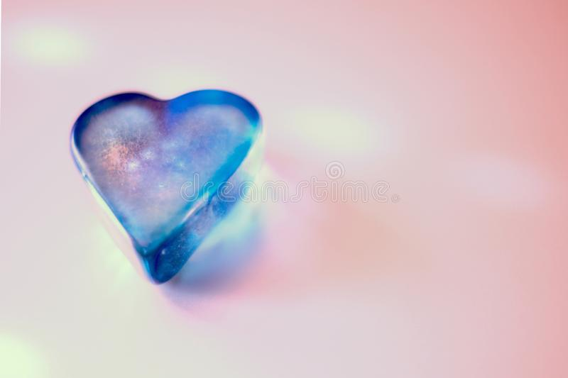 Closeup shot of a blue crystal heart pebble on a pink surface royalty free stock photography